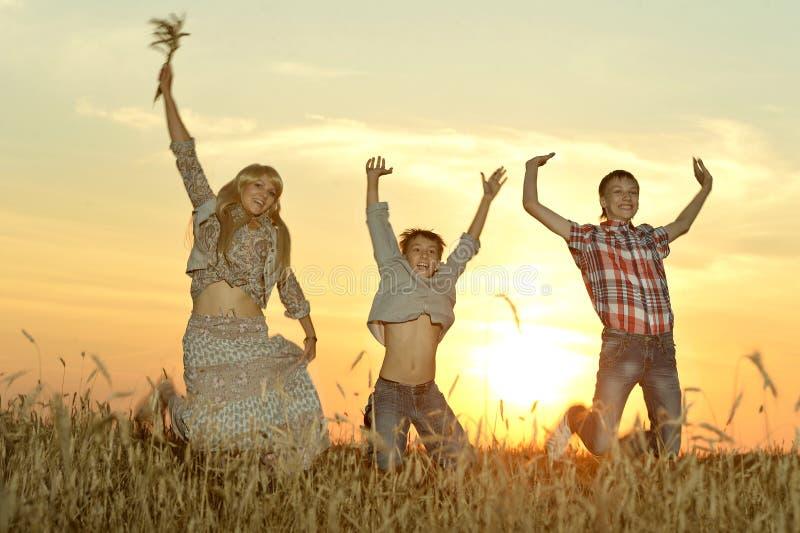 Семья скача в поле в вечере стоковые фотографии rf