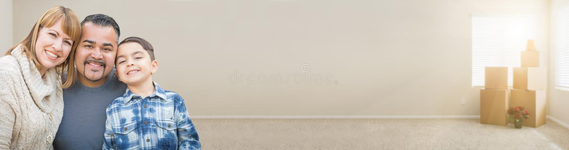 Семья смешанной гонки в пустой комнате с Moving знаменем коробок стоковое фото rf