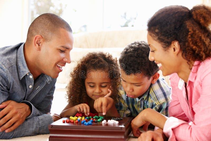 Семья смешанной гонки играя пасьянс стоковое фото rf