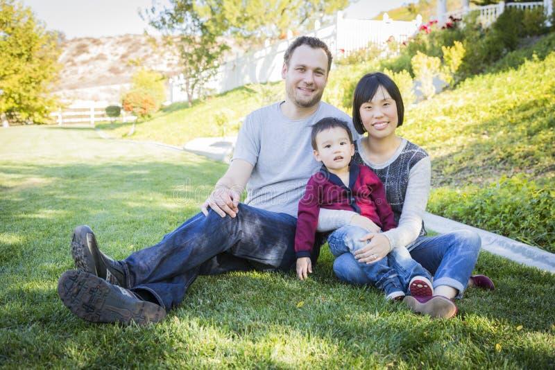 Семья смешанной гонки имея потеху снаружи стоковая фотография