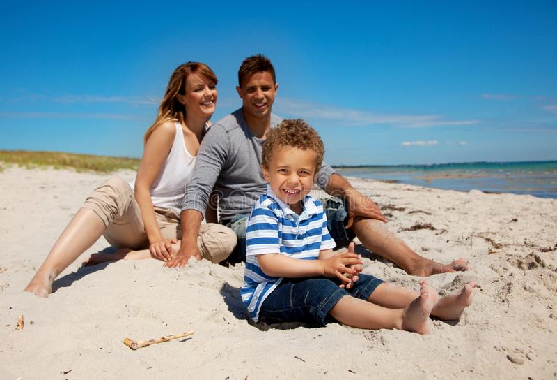 Семья смешанной гонки смотря счастлива на пляже стоковое фото rf