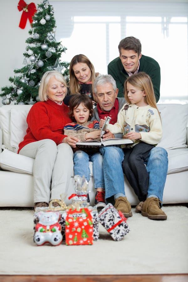 Семья смотря книгу в доме стоковые фото