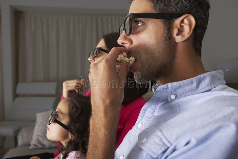 Семья смотря ТВ нести стекла 3D и съесть попкорн стоковая фотография rf