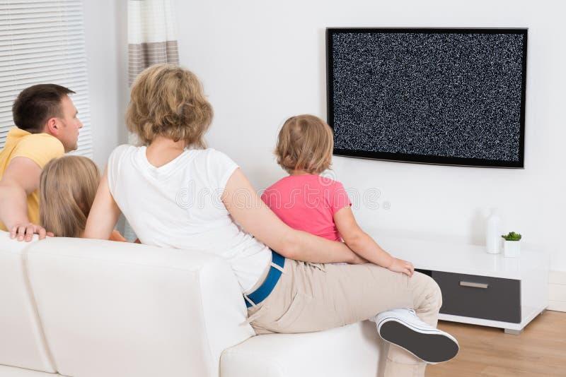 Семья смотря телевидение не показать никакой сигнал стоковое фото rf