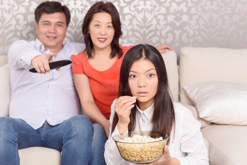 Семья смотря фильмы дома стоковые изображения