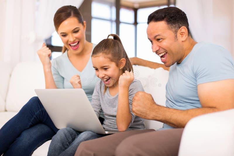 Семья смотря экран компьтер-книжки стоковые изображения