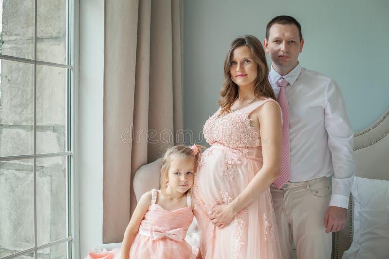 семья счастливая Беременная дочь матери, отца и ребенка дома стоковые фотографии rf