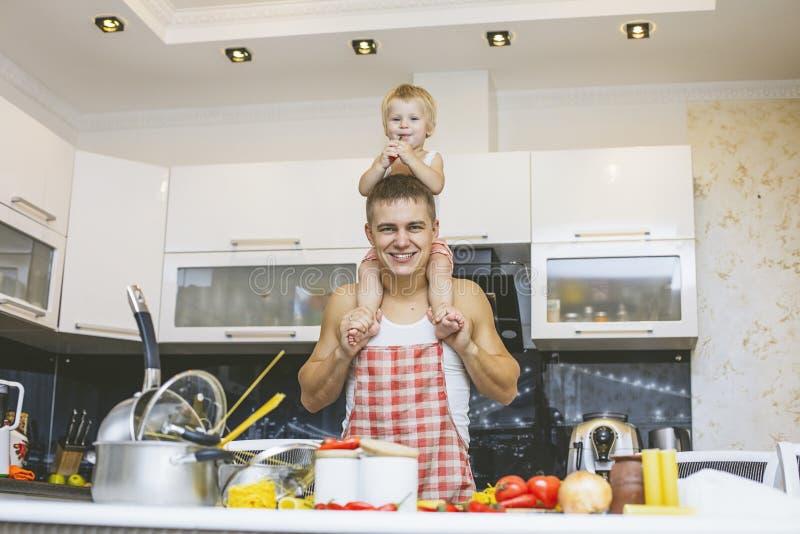 Семья, счастливая дочь при папа в домашней кухне смеясь над и pre стоковая фотография rf