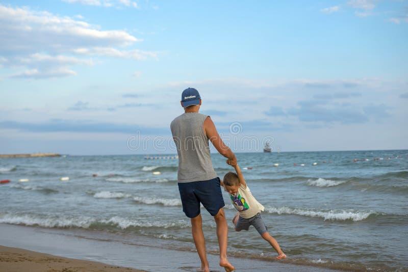 семья счастливая Молодой красивый отец и его усмехаясь ребёнок сына имея потеху на пляже моря, океана Положительное человеческое  стоковое изображение rf