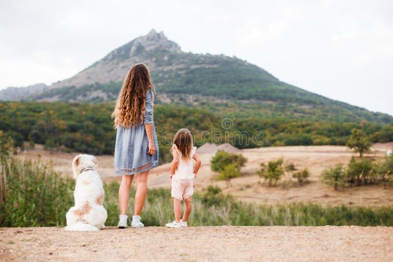 Семья с большой собакой и малым ребенком в горах задний взгляд Космос для текста стоковое изображение rf