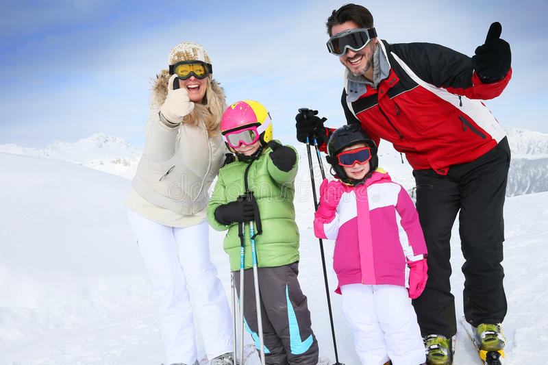 Семья с большими пальцами руки вверх на праздники снега в лыжном курорте стоковое изображение rf
