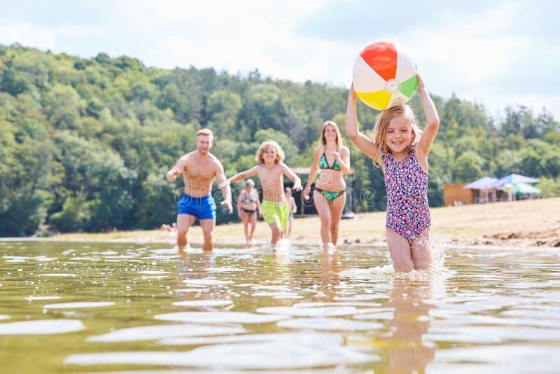 Семья с 2 детьми играет с шариком стоковые фотографии rf