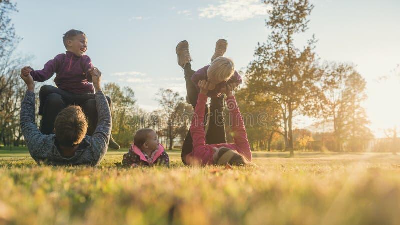 Семья с 3 детьми имея потеху в парке осени стоковые изображения