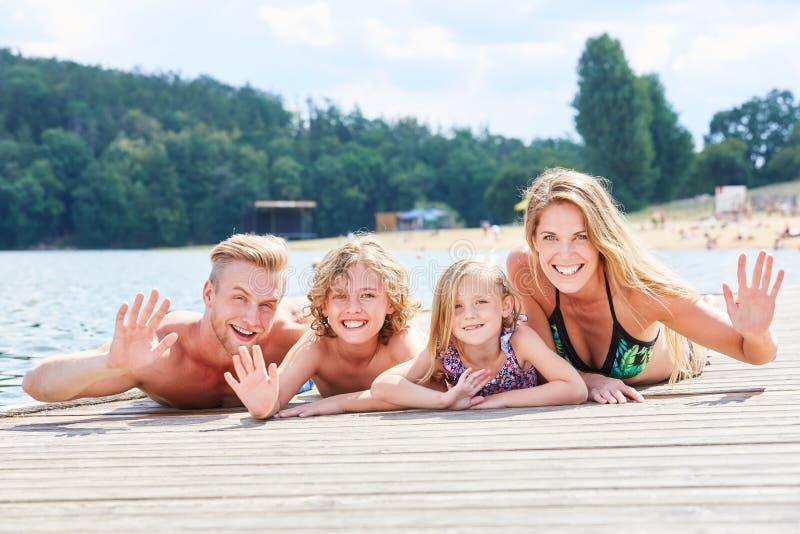 Семья с 2 детьми на моле на озере стоковые изображения rf