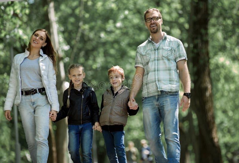 Семья с 2 детьми на прогулке в парке стоковая фотография