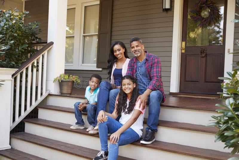 Семья с детьми сидит на шагах водя до крылечка дома стоковое фото rf