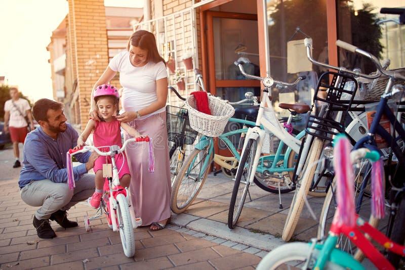 Семья с дочерью имея велосипед и шлемы потехи на открытом воздухе ходя по магазинам новый стоковое фото