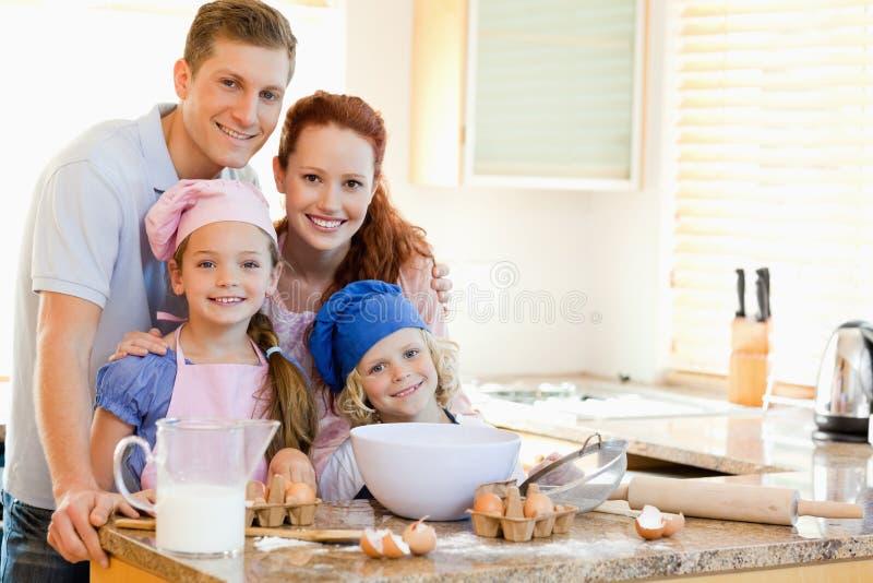 Семья с ингридиентами выпечки за счетчиком кухни стоковое изображение