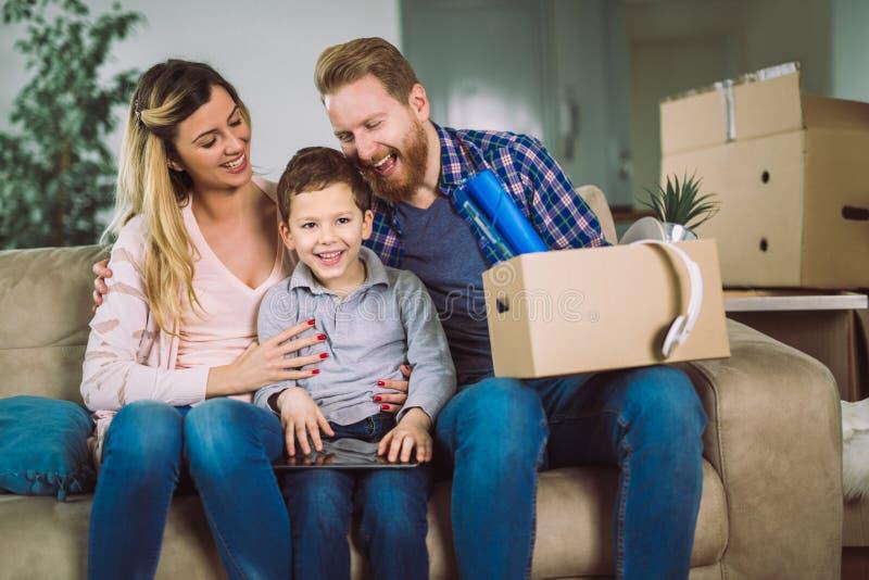 Семья с картонными коробками в новом доме на moving дне стоковая фотография