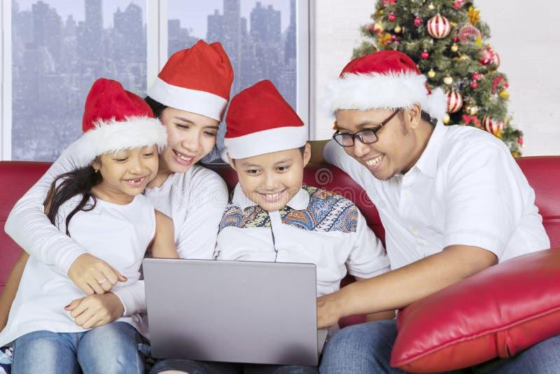 Семья с компьтер-книжкой пользы шляпы Санты на кресле стоковое изображение rf