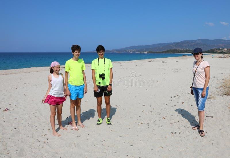 Семья с матерью и тремя детьми на пляже стоковое изображение rf