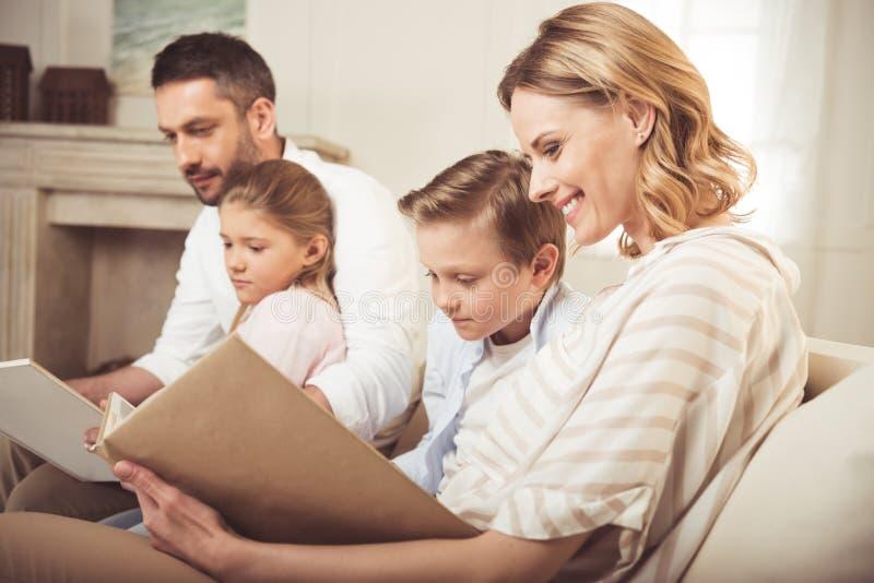 Семья с 2 прелестными детьми сидя совместно и книгами чтения дома стоковые фотографии rf