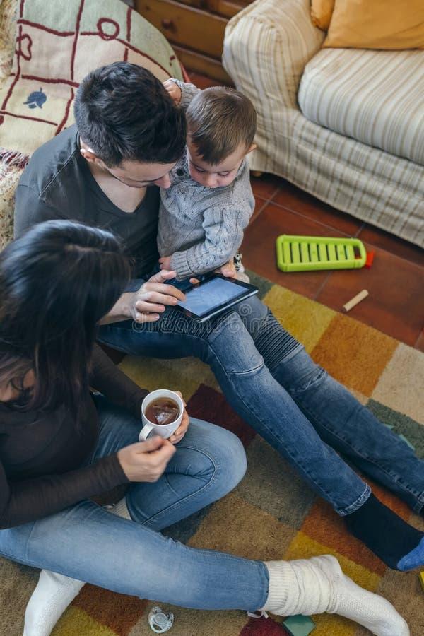 Семья с ребенком и беременная будут матерью смотреть таблетку стоковые фотографии rf