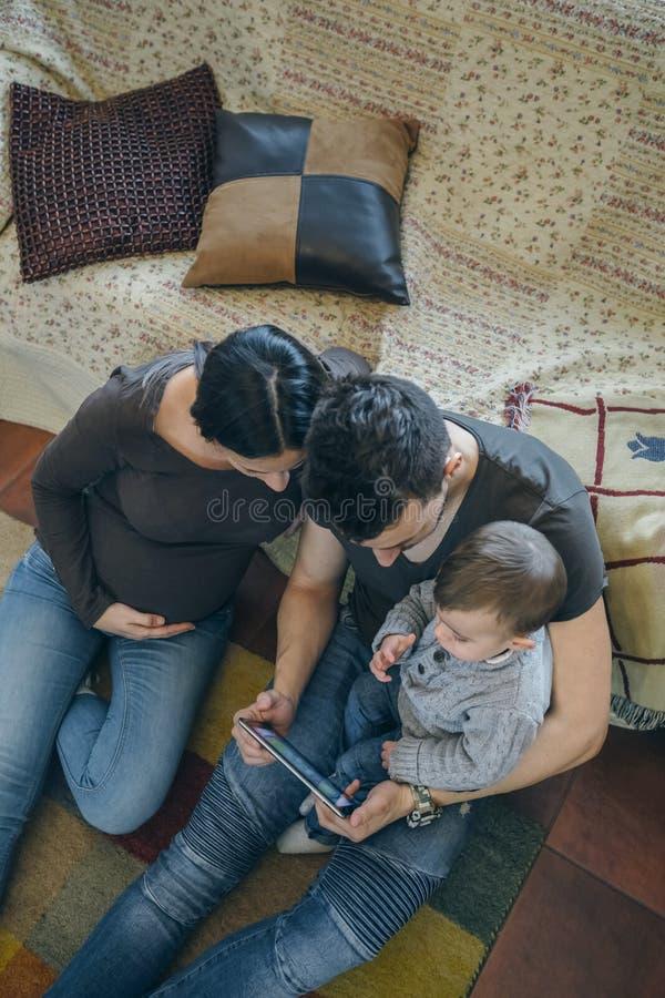 Семья с ребенком и беременная будут матерью смотреть таблетку стоковая фотография
