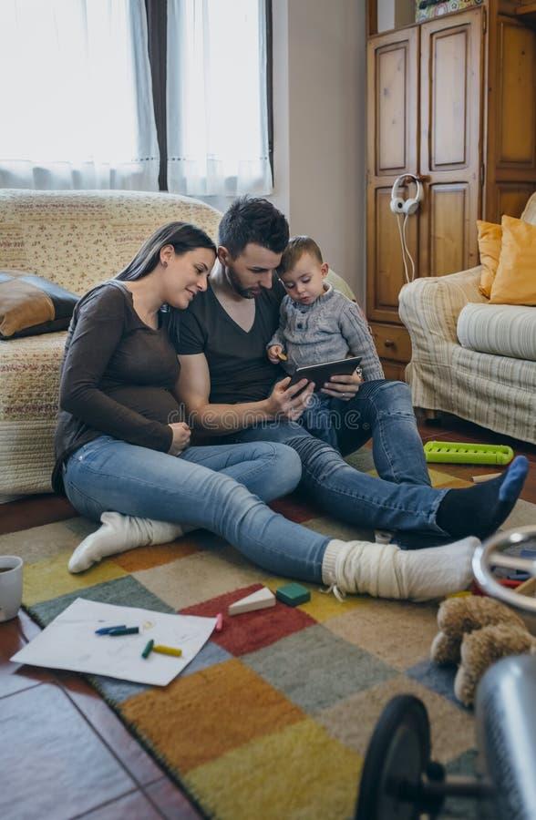 Семья с ребенком и беременная будут матерью смотреть таблетку стоковое фото rf