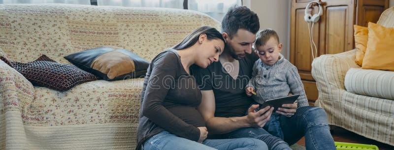 Семья с ребенком и беременная будут матерью смотреть таблетку стоковые фото