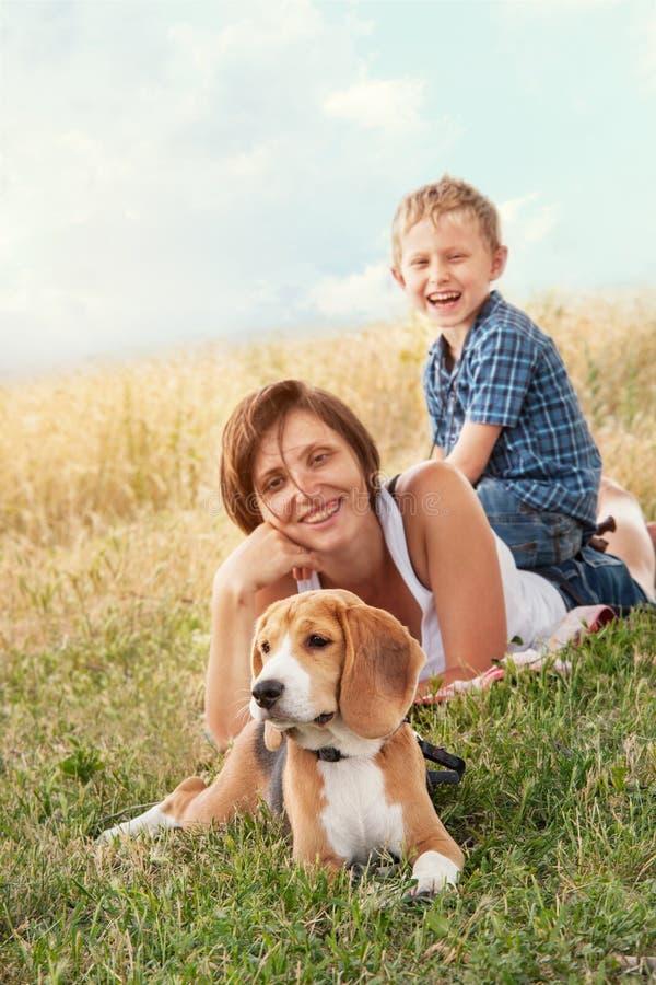 Семья с собакой имеет спокойные часы досуга внешние стоковое фото rf