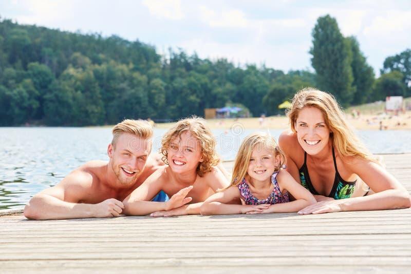 Семья с сыном и дочерью на моле на озере стоковая фотография