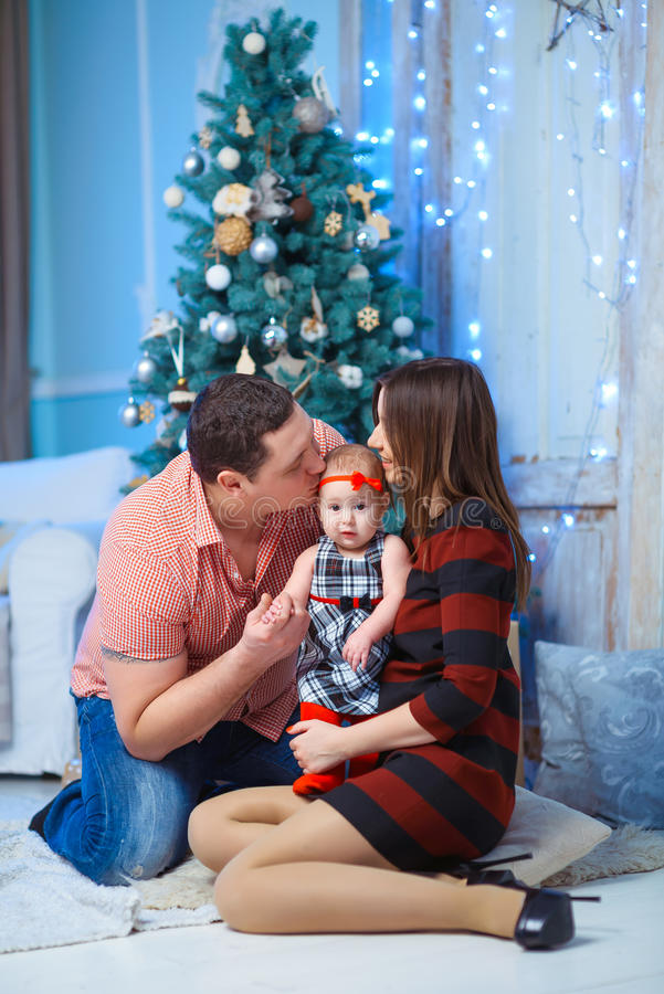 Семья с целовать ребенк Счастливые усмехаясь родители и стоковое изображение rf