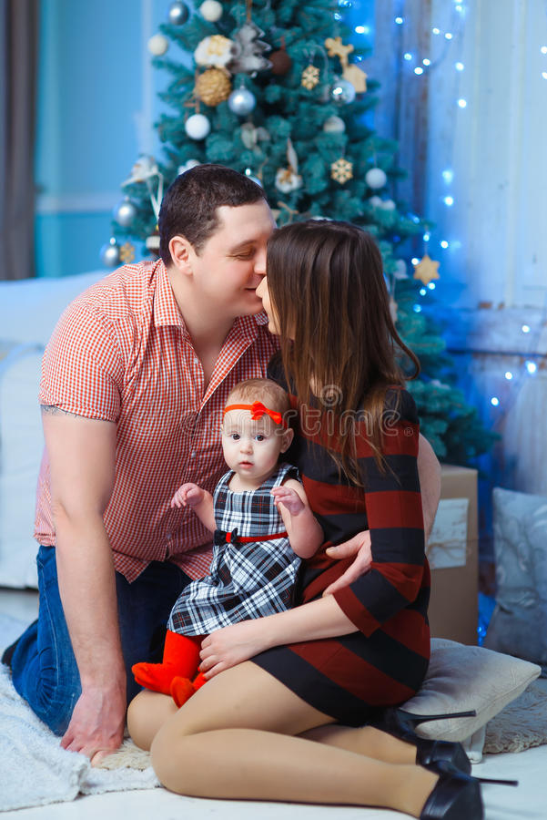 Семья с целовать ребенк Счастливые усмехаясь родители и стоковые фотографии rf