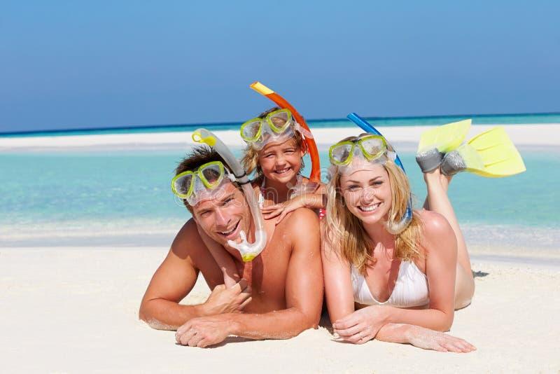 Семья с шноркелями наслаждаясь праздником пляжа стоковые фото