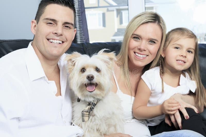 Семья с любимчиками сидит на софе дома стоковые фото