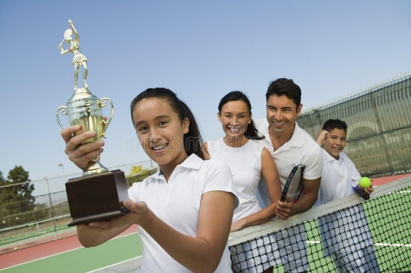 Семья тенниса на суде сетчатой дочерью держа портрет трофея стоковые фотографии rf