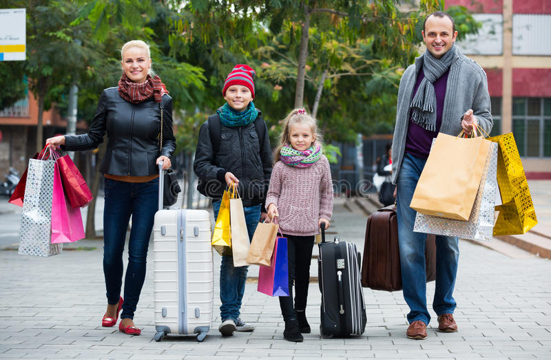 Семья туристов нося хозяйственные сумки стоковые изображения