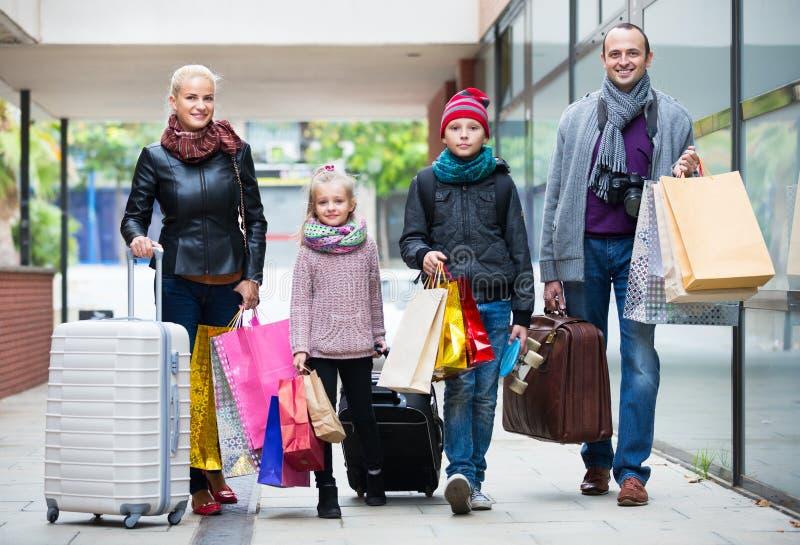 Семья туристов нося хозяйственные сумки стоковое фото rf