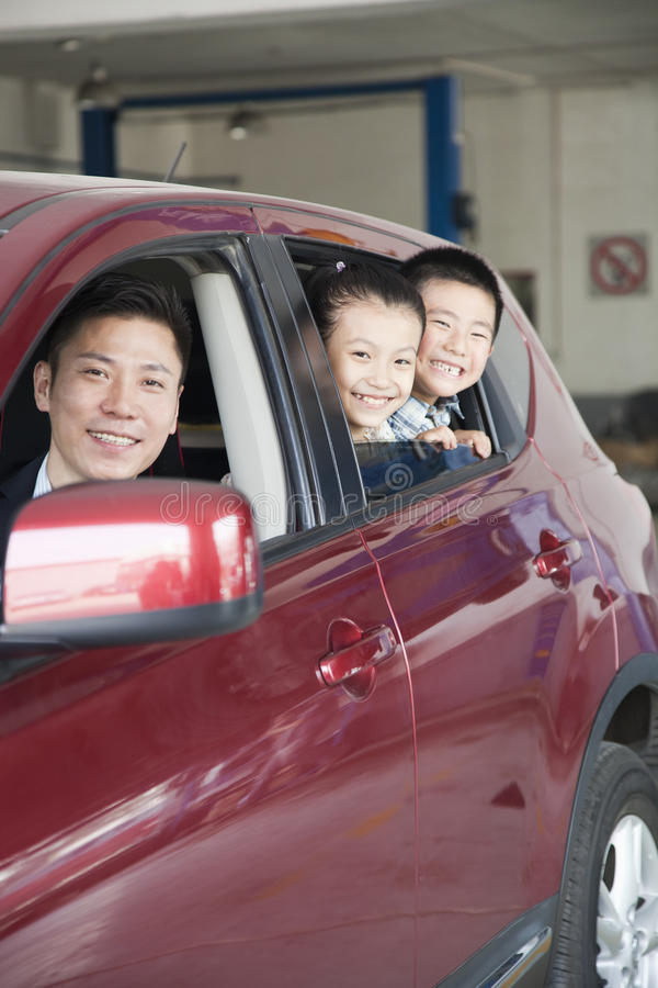 Семья усмехаясь смотрящ вне окно автомобиля, смотря камеру стоковое изображение rf