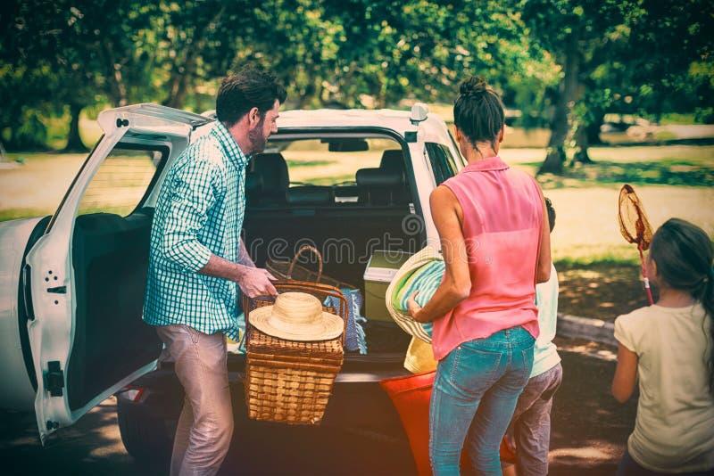 Семья устанавливая детали пикника в багажнике автомобиля стоковая фотография rf