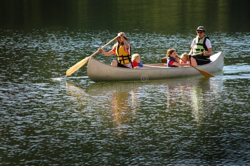 Семья Canoeing совместно на озере в глуши стоковые фотографии rf