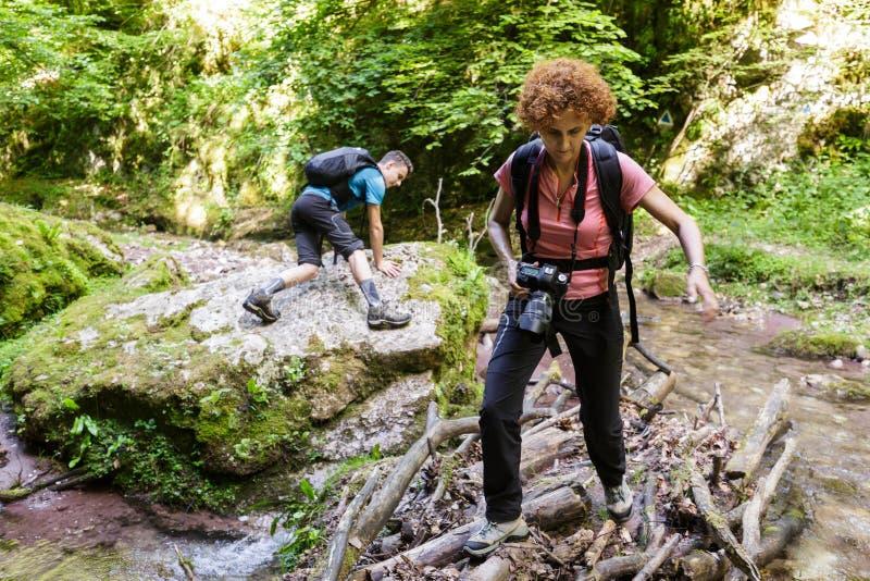Семья hikers пересекая реку стоковое фото rf