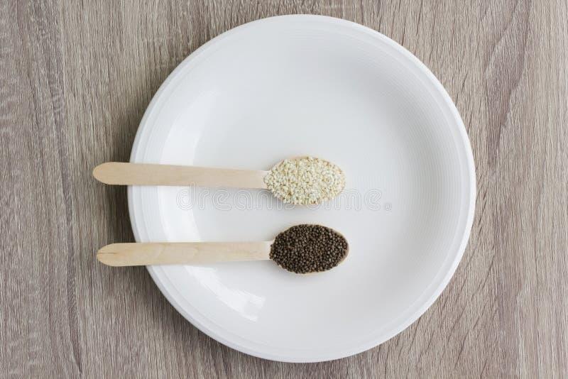 Семя frutescens сезама и perilla Topview белое для здорового на деревянной ложке на белом блюде на деревянном столе стоковое фото