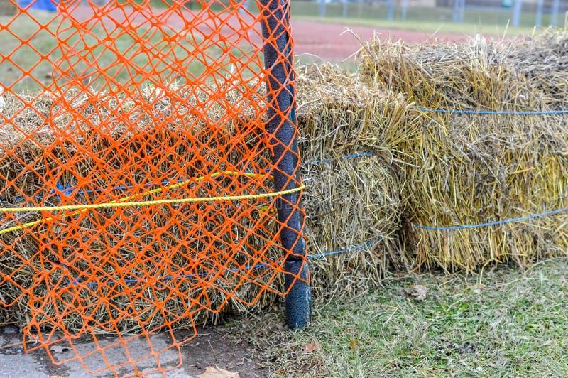 Сено за оранжевой сетчатой загородкой стоковое фото rf