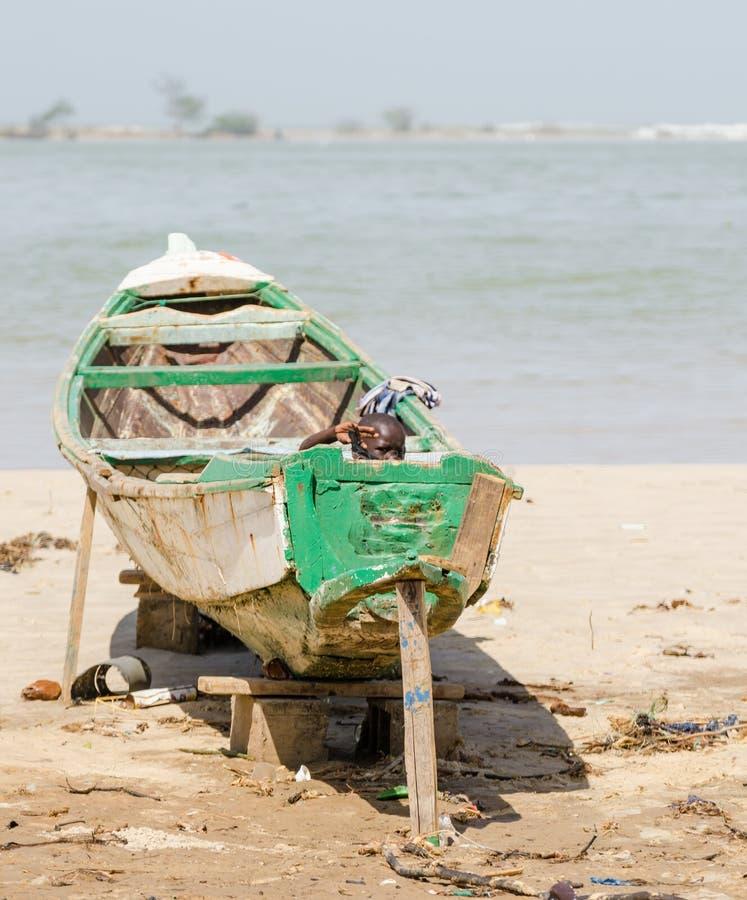 Сент-Луис, Сенегал - 20-ое октября 2013: Неопознанный молодой африканский мальчик пряча в деревянной шлюпке и развевать стоковое фото rf