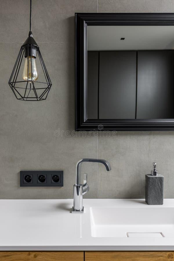 Серая ванная комната с зеркалом стоковые изображения rf