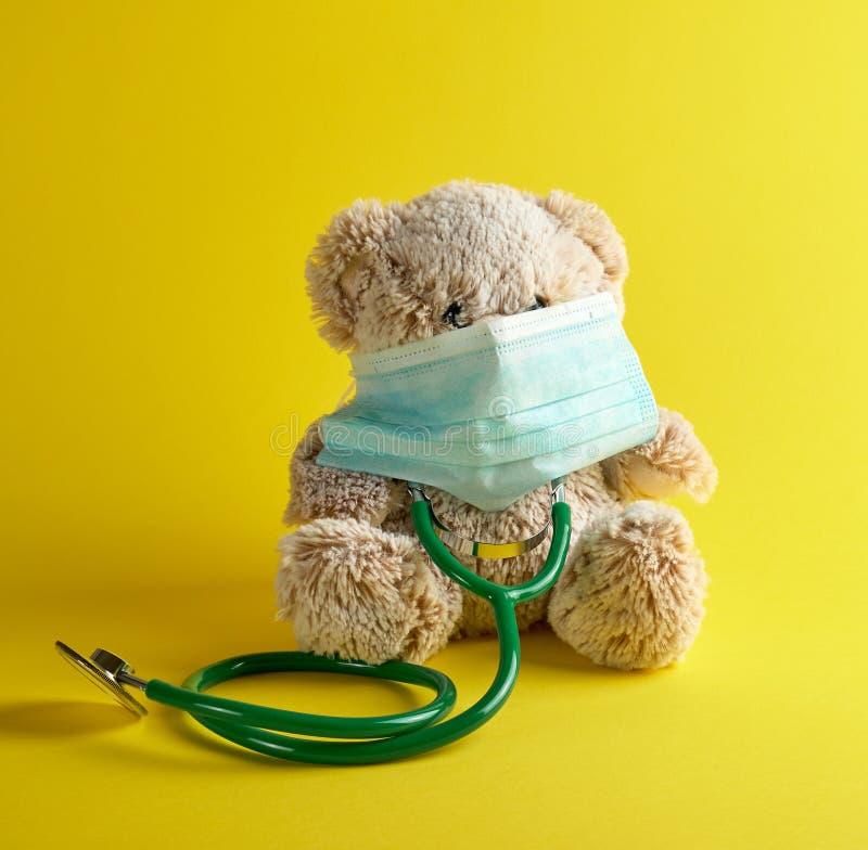 серая плюшевый мишка и зеленый медицинский стетоскоп стоковая фотография