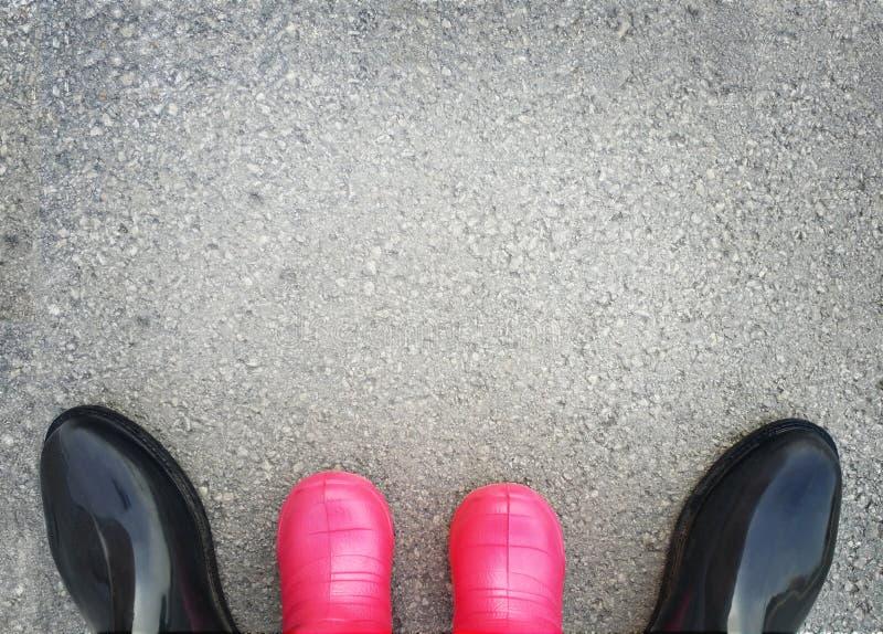 Серая предпосылка с текстурой асфальта, взрослыми и ботинками детей резиновыми стоковая фотография