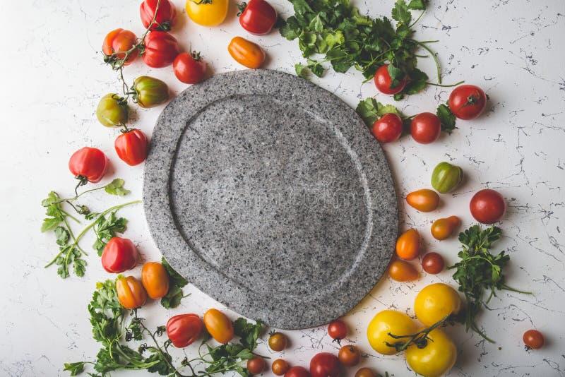 Серая пустая каменная плита и свежие варя ингридиенты - зеленый цвет красные, желтые оранжевые томаты и травы Изображения космоса стоковое изображение